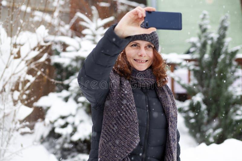 kvinna som tar en selfie i snö royaltyfria bilder