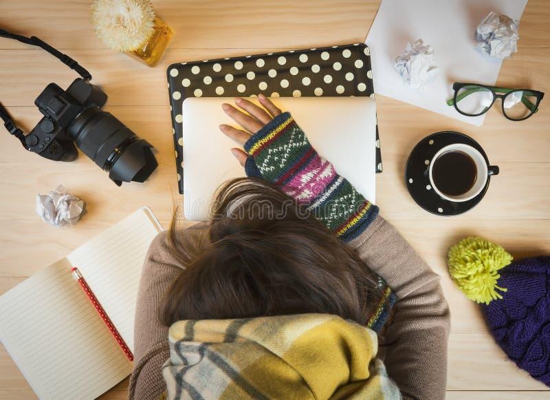 Kvinna som tar en ta sig en tupplur på skrivbordet med arbetsmaterial royaltyfria foton