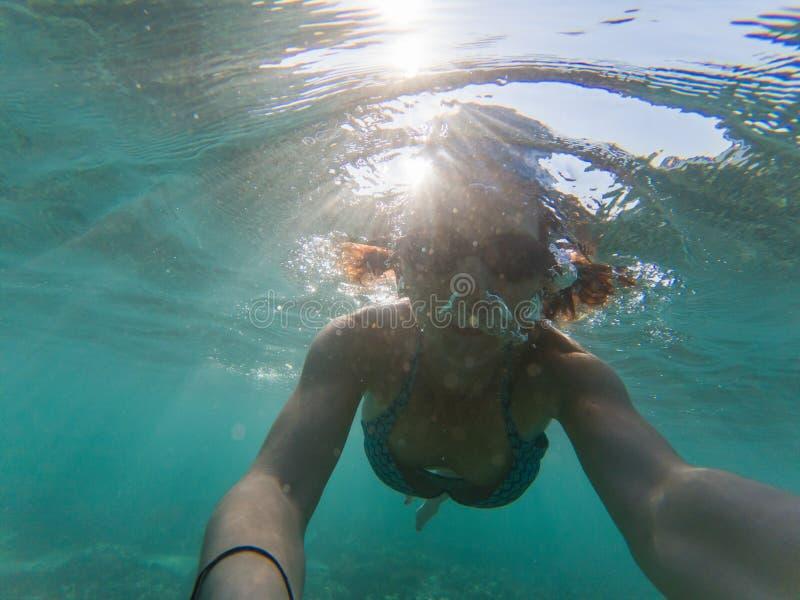 kvinna som tar en undervattens- selfie, medan snorkla i kristallklart tropiskt vatten royaltyfri fotografi