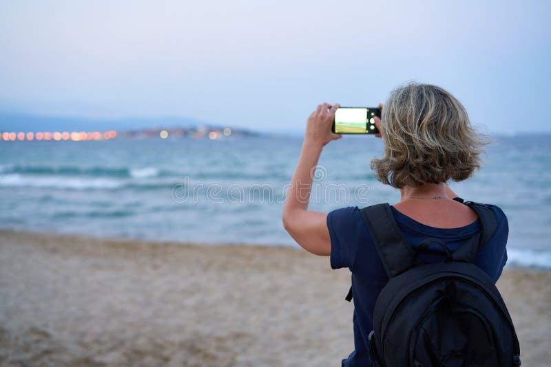 Kvinna som tar ett foto av ett hav p? den smarta telefonen p? solnedg?ng royaltyfri foto
