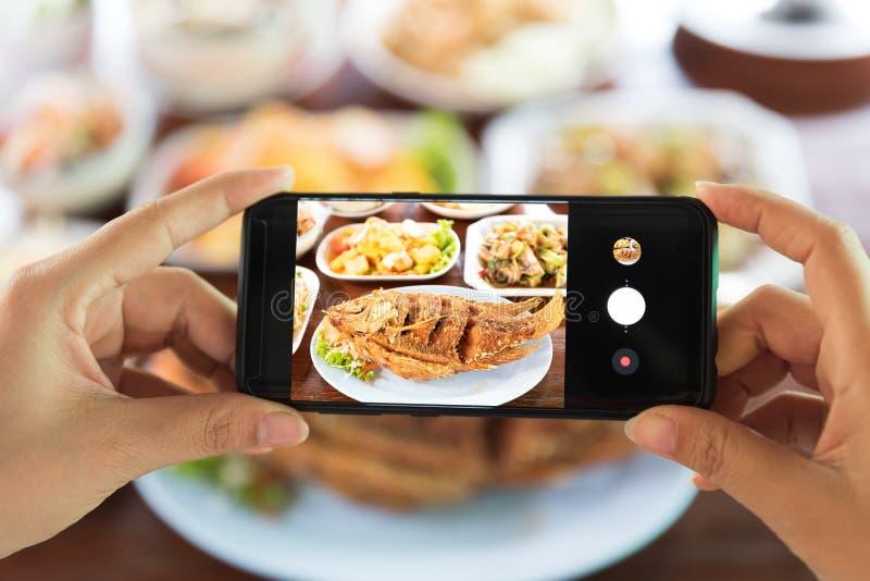 Kvinna som tar ett foto av mat med smartphonen i restaurang royaltyfri bild