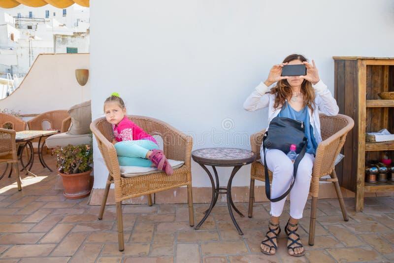 Kvinna som tar ett foto med smartphonen i terrass- och flickamaken arkivbild