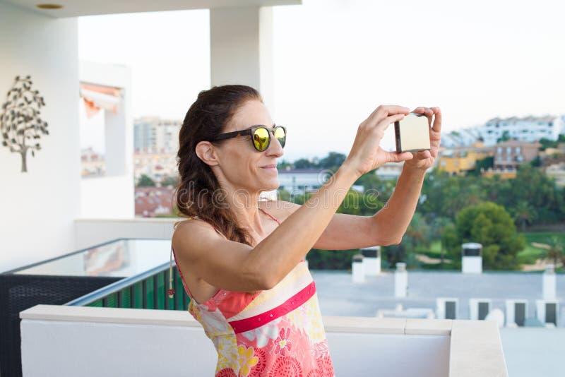 Kvinna som tar ett foto med smartphonen i terrassen royaltyfri foto