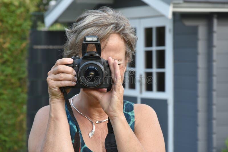 Kvinna som tar foto med en reflexkamera arkivfoto