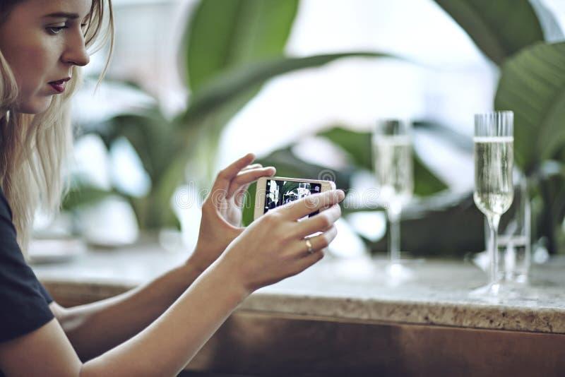 Kvinna som tar fotoet av champagne i exponeringsglas Möte i stadsrestaurang eller kafé Houseplants near fönstret, dagsljus royaltyfri fotografi