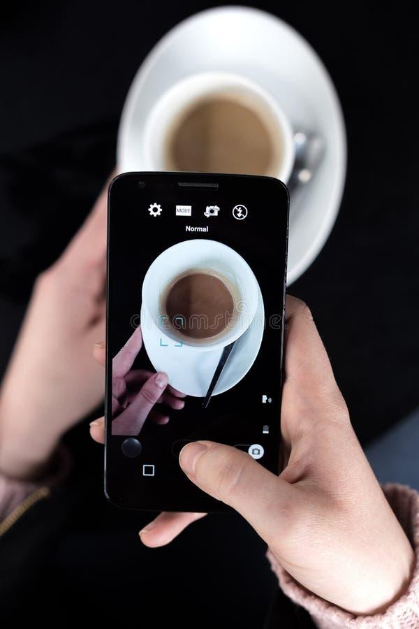 Kvinna som tar fotoet av en kopp kaffe på hennes smartphone för sociala nätverk arkivbilder