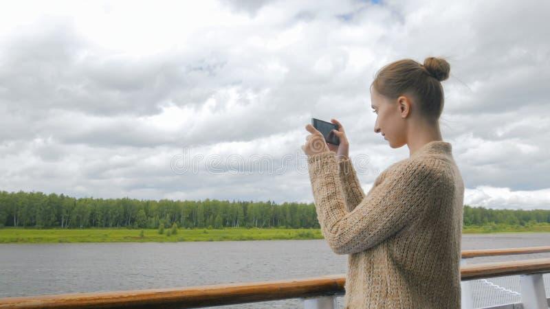 Kvinna som tar fotoet av landskapet med smartphonen på däck av kryssningskeppet royaltyfri bild