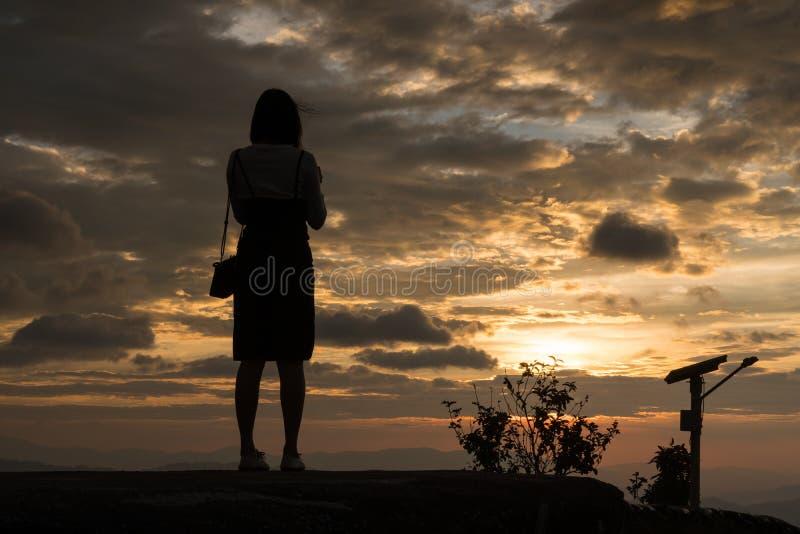 Kvinna som tar fotoet i solnedgång arkivbilder