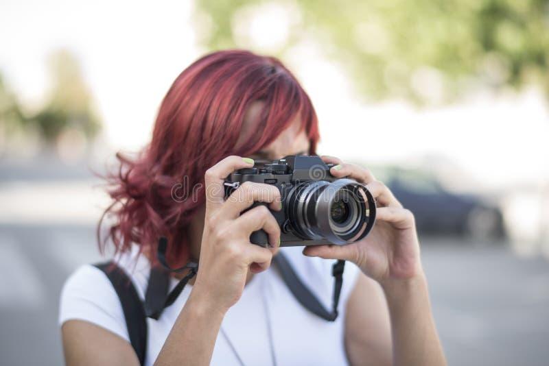 Kvinna som tar fotoet med den mirroless kameran arkivbild