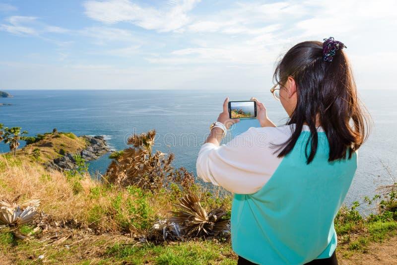 Kvinna som tar fotografiet med smartphonen fotografering för bildbyråer