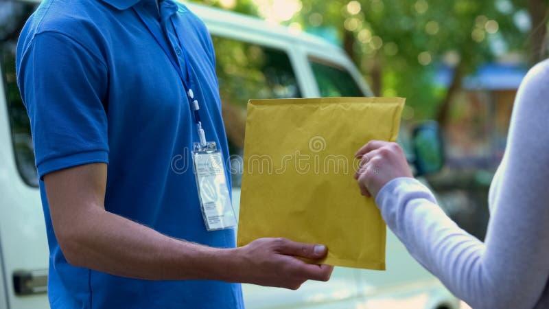 Kvinna som tar kuvertet med dokument från delivererhänder, dörr-till-dörr sändning arkivbild