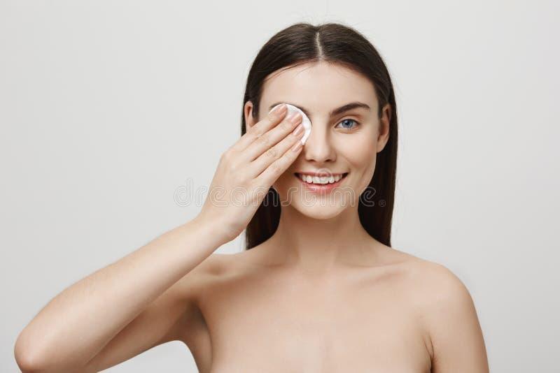 Kvinna som tar omsorg av hennes hud att hålla den härlig Studion sköt av den attraktiva caucasian flickan som av tar mascara med royaltyfri fotografi
