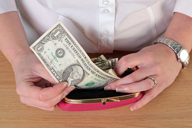 Kvinna som tar pengar ut ur hennes handväska royaltyfria foton
