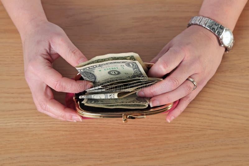 Kvinna som tar pengar ut ur hennes handväska royaltyfri fotografi