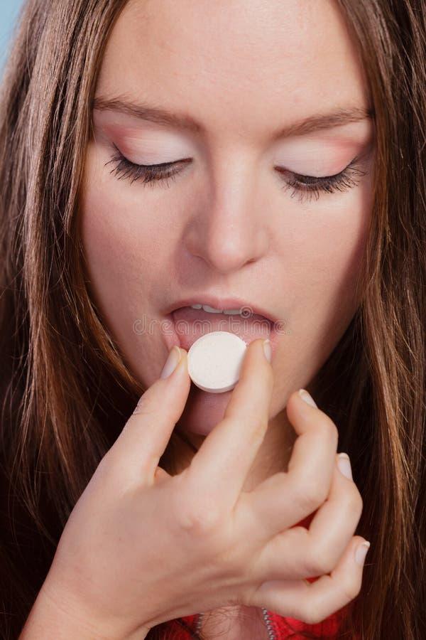 Kvinna som tar smärtstillande medelpreventivpillerminnestavlan isolerade fängelsekunder för armomsorg hälsa royaltyfri fotografi