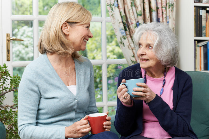 Kvinna som tar Tid till grannen och samtalet för besök den höga kvinnliga fotografering för bildbyråer