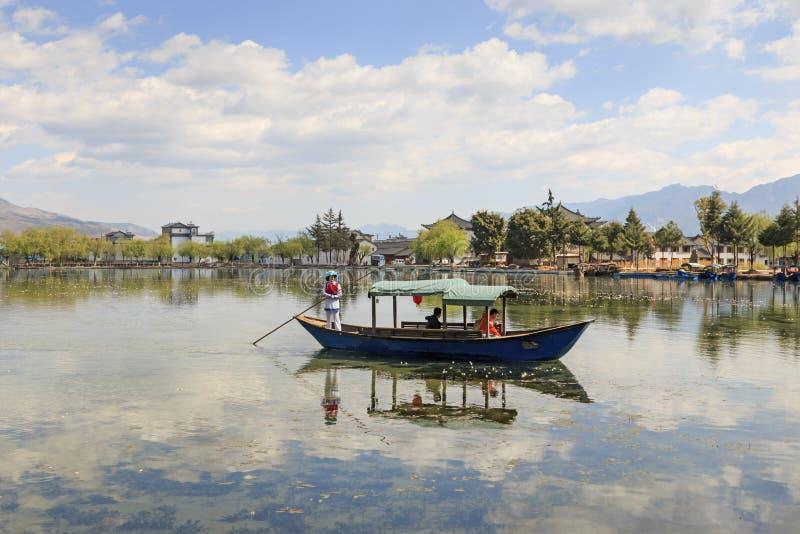 Kvinna som tar turister på en fartygritt i Heqing, Yunnan royaltyfria bilder