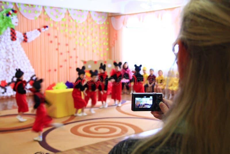 Kvinna som tar videoen av barns morgonpartiet Barn på matiné på dagiset royaltyfri foto
