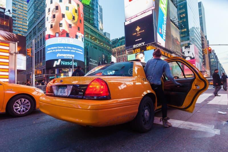 Kvinna som tidvis får in i en gul fyrkant för taxi, NYC fotografering för bildbyråer
