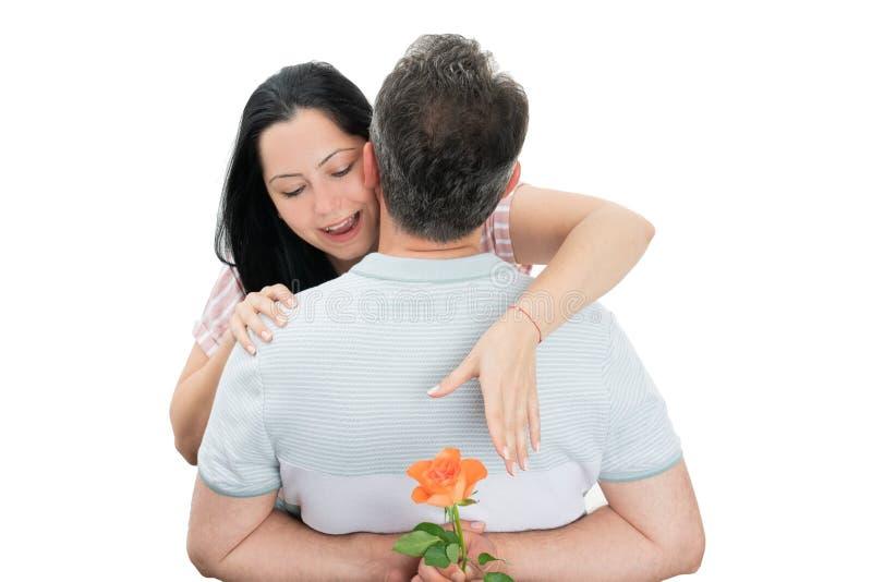Kvinna som tillbaka når på rosen bak man arkivbild