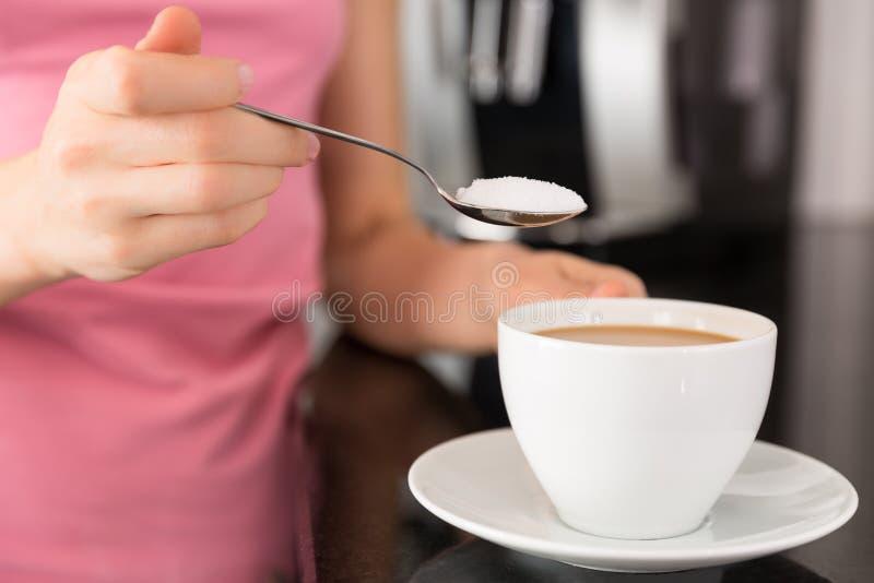 Kvinna som tillfogar socker till kaffet arkivbilder