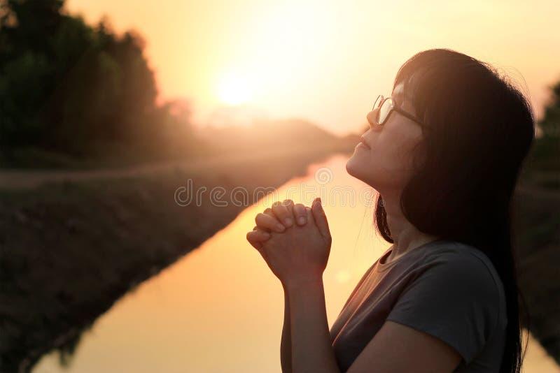 Kvinna som tillsammans ber med händer på natursolnedgång royaltyfri foto