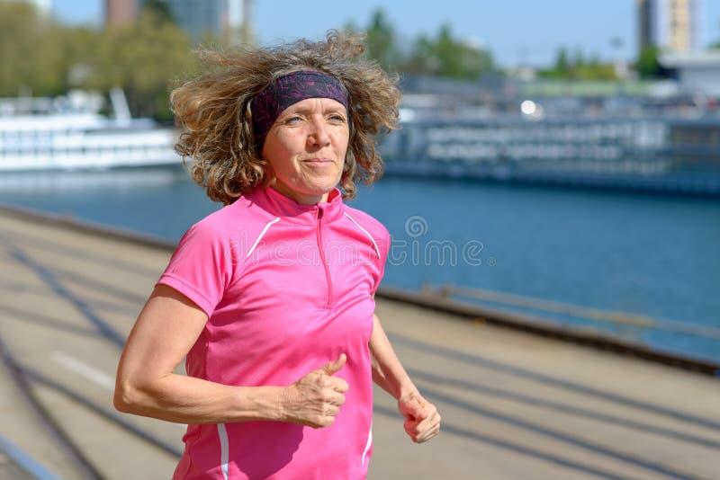 Kvinna som tillsammans med joggar en stads- kanal eller flod arkivbilder