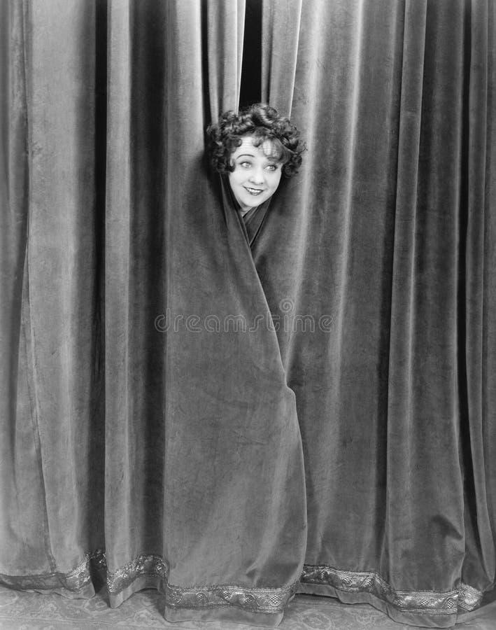 Kvinna som titt-en-buar bak en gardin (alla visade personer inte är längre uppehälle, och inget gods finns Leverantörgarantier so arkivbilder