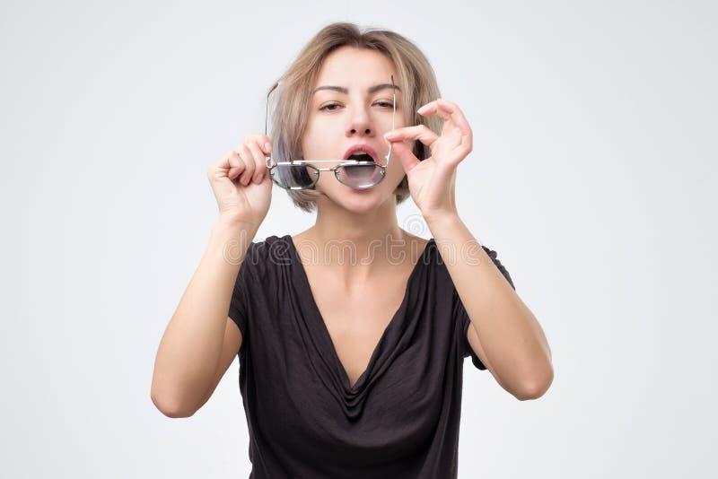 Kvinna som torkar hennes exponeringsglas som gör dem ren damm royaltyfri foto