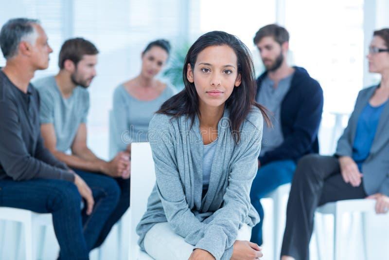 Kvinna som tröstar andra i rehabgrupp på terapi royaltyfri foto