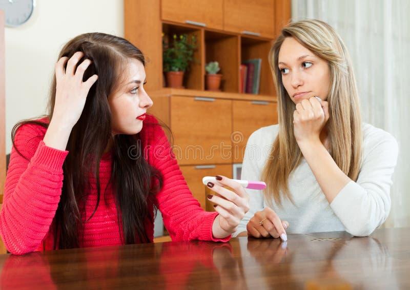 Kvinna som tröstar den deprimerade vännen med graviditetstestet arkivbild