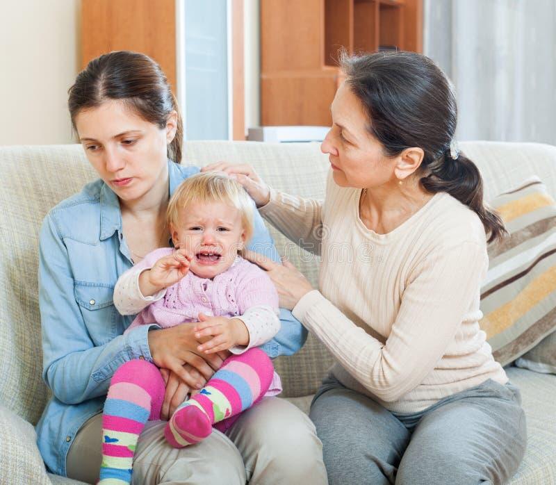 Kvinna som tröstar den vuxna dottern med lilla barnet arkivfoto