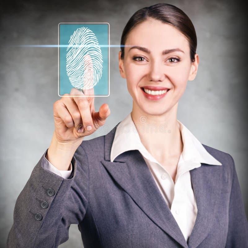 Kvinna som trycker på på den faktiska knappen med dactyloscopybildläsaren royaltyfria foton