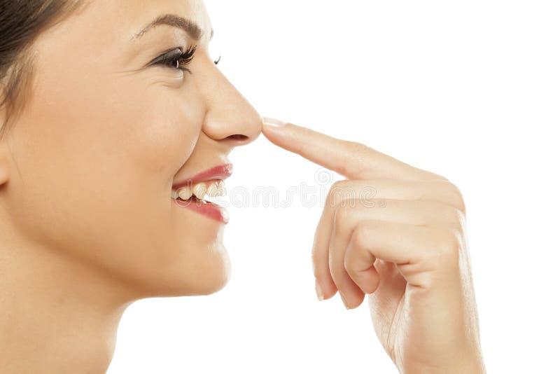 Kvinna som trycker på hennes näsa royaltyfri bild