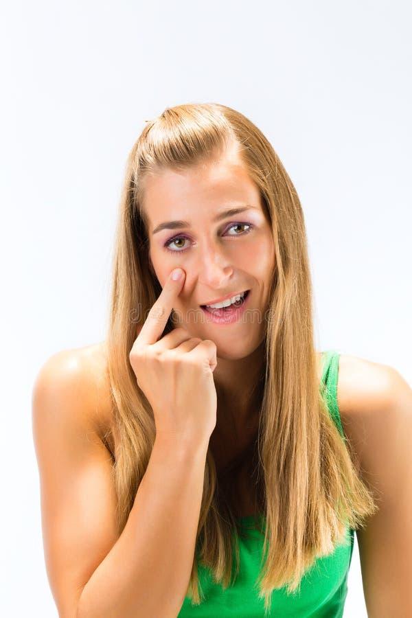 Kvinna som trycker på huden under hennes öga arkivbild