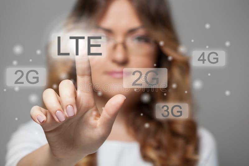 Kvinna som trycker på LTE-pekskärmknappen arkivfoto
