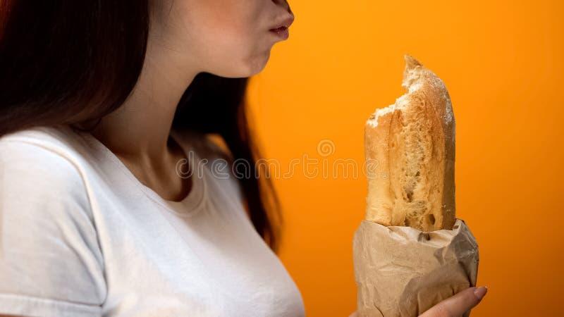 Kvinna som tuggar nytt bröd, upptagen livsstil, brist av tid för riktig näring arkivbilder