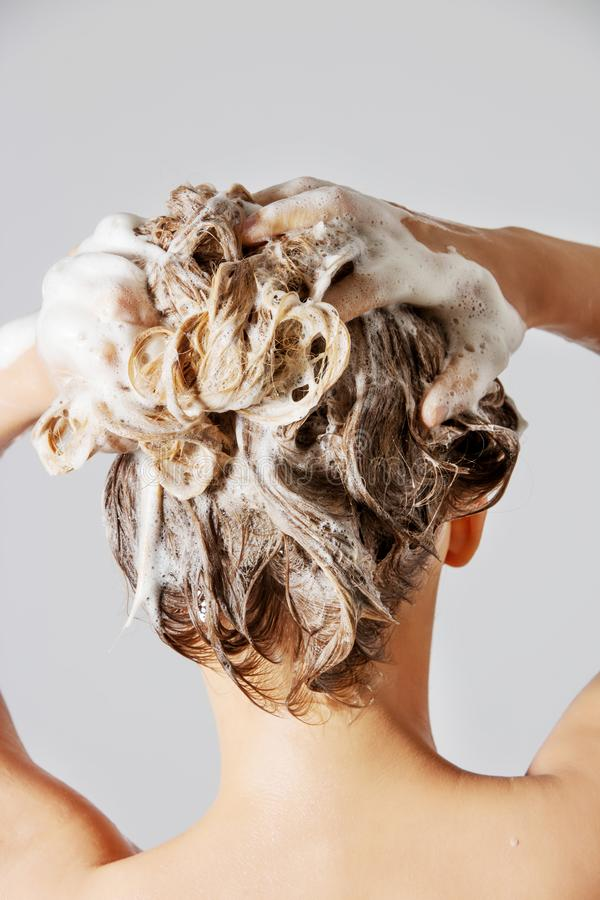 Kvinna som tvättar hennes blonda hår royaltyfri foto