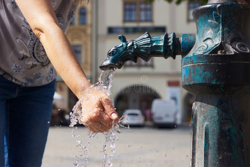 Kvinna som tvättar hennes händer i en offentlig vattenpump i staden royaltyfria bilder