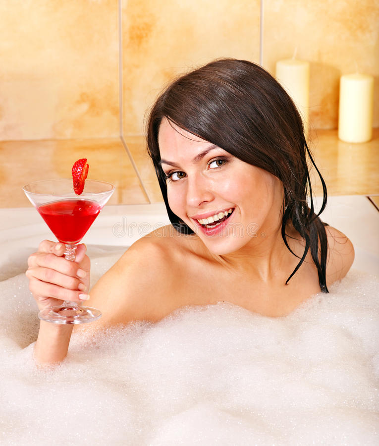 Kvinna som tvättar sig i bubbelbad. arkivbild