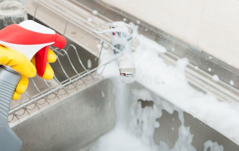 Kvinna som tvättar vasken med att desinficera sprej royaltyfria foton