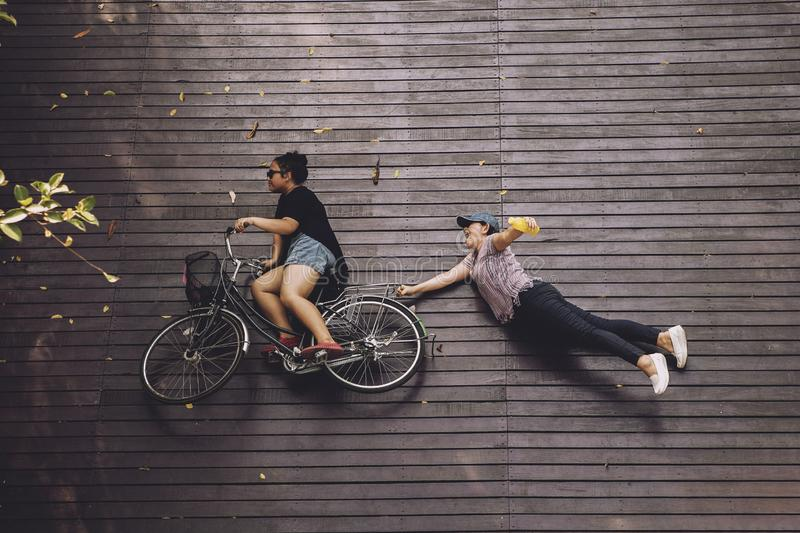Kvinna som två lurar ritt på cykeln över den wood terrassen fotografering för bildbyråer