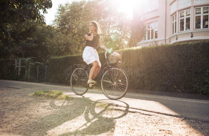 Kvinna som tycker om cykelritt till och med gatan arkivfoton