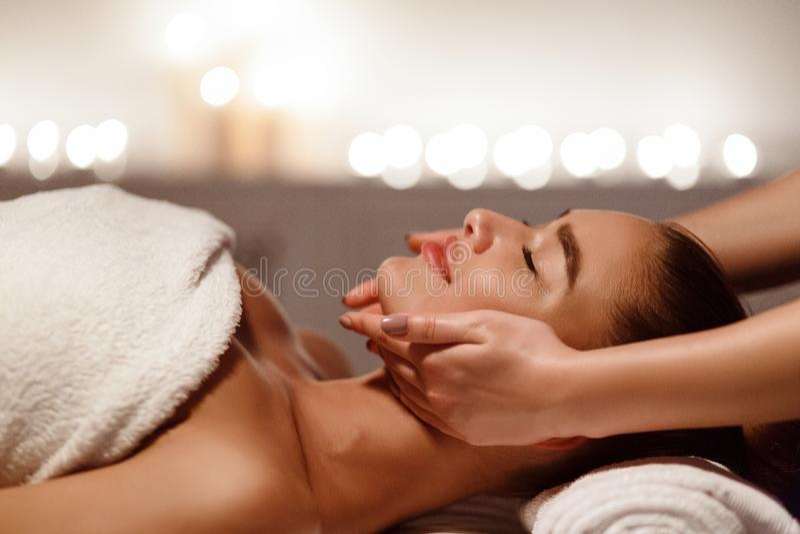 Kvinna som tycker om den anti-åldras ansikts- massagen, sidosikt arkivfoton
