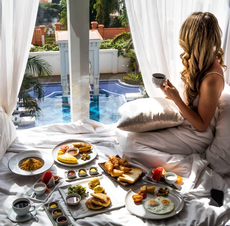Kvinna som tycker om den lyxiga semesterfrukosten - exotisk hotellloppflykt arkivbild