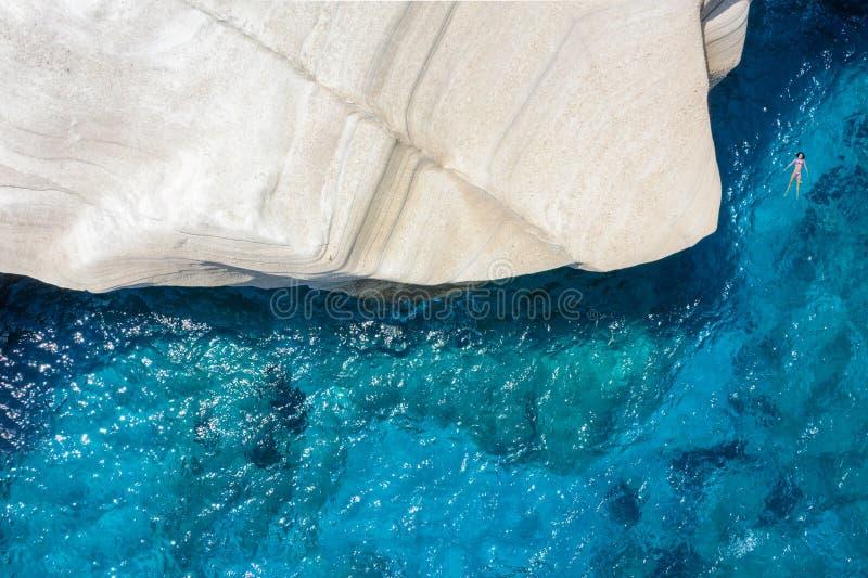 Kvinna som tycker om det blåa havet till den Sarakiniko stranden på Milos ö, Cyclades, Grekland royaltyfri fotografi