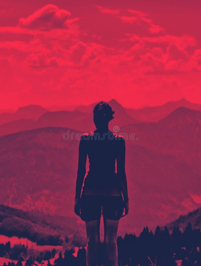 Kvinna som tycker om en dramatisk röd solnedgång royaltyfria bilder