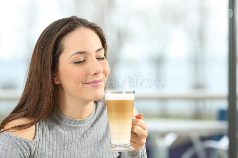 Kvinna som tycker om ett macchiatokaffe royaltyfri fotografi