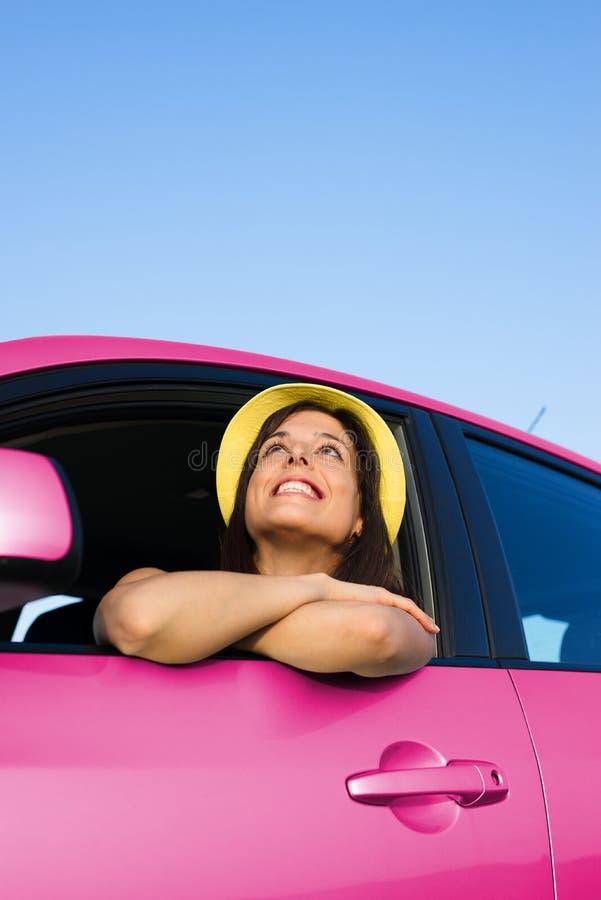 Kvinna som tycker om frihet med hennes rosa bil royaltyfri foto