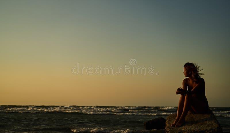 Kvinna som tycker om härlig solnedgång på stranden fotografering för bildbyråer